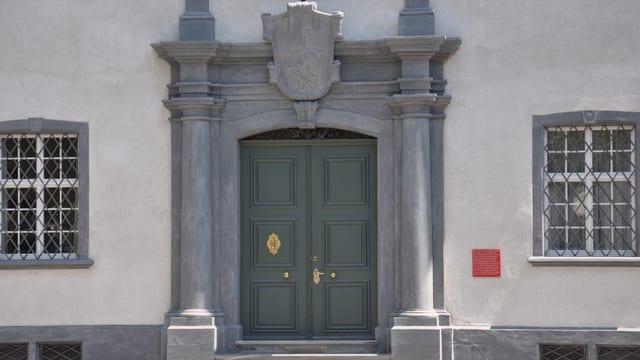 La porta en l'uschènumnada Chasa Grischa ch'è la sedia da la regenza grischuna a Cuira.