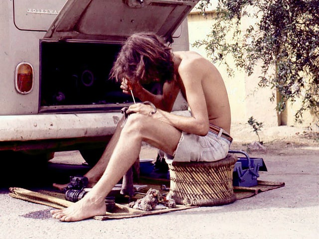 Ein junger Mann repariert vor seinem VW-Bus eine Zündkerze. Er hält einen Schraubenzieher in der Hand.