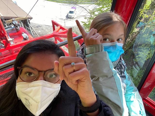 Julia und Riana in der Gondel und zeigen auf den Zambo-Bus.