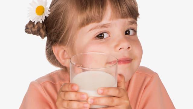 EIn Mädchen mit einem Glas Milch in der Hand.