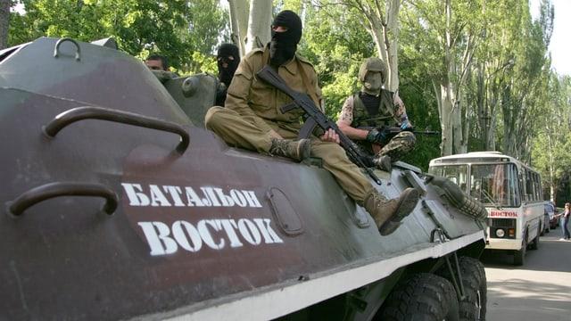 Vermummte Separatisten mit Gewehern auf einem Panzer.