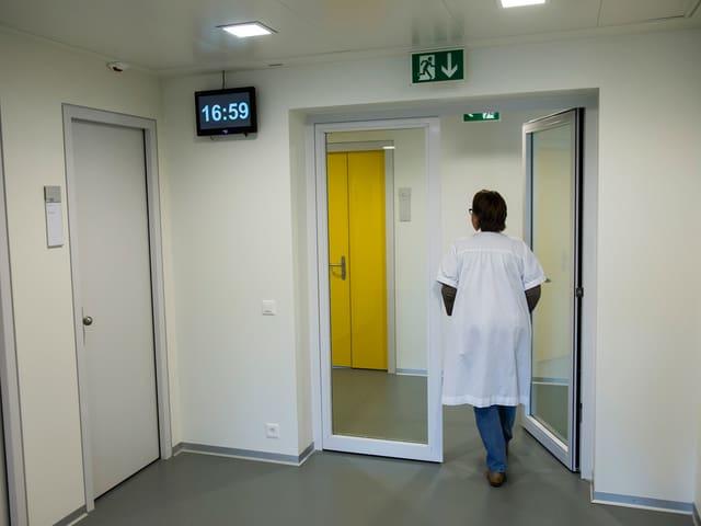 Eine Frau läuft durch die Gänge einer Psychiatrie.