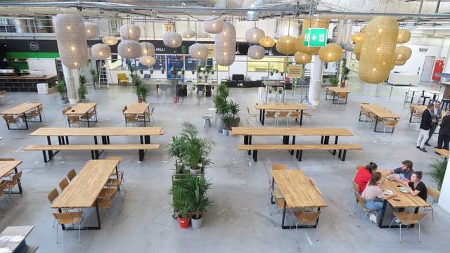 Eine grosse Halle mit Tischen, Bänken und Stühlen.