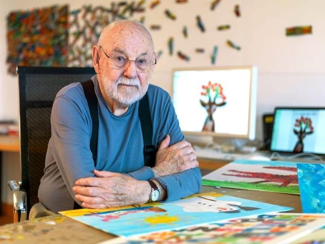 Ein älterer Herr mit Glatze und blauem Pullover sitzt an einem Schreibtisch, auf dem bunte Bilder liegen.