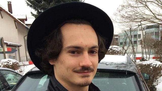 Mann mit Schnauz und Hut im Porträt.