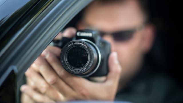 Purtret d'in detectiv che fa ina fotografia or d'in auto.