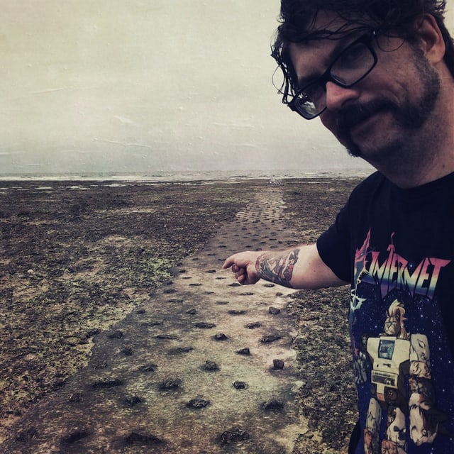 Guido steht am Strand und zeigt auf den Kabelkanal aus Beton. Er trägt ein T-Shirt mit der Aufschrift «Internet».