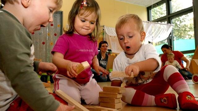Kleine Kinder spielen am Boden.
