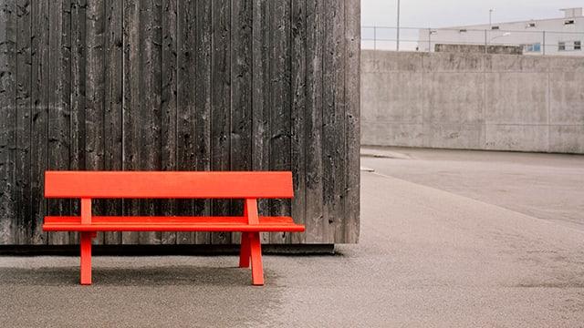 Eine roter Holzbank vor einer Holzwand.