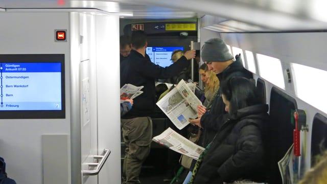 Pendler stehen in der S-Bahn.