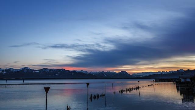 Abendstimmung am See mit Bergen im Hintergrund