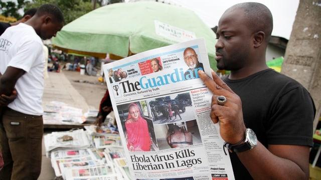 Mann liest Zeitung mit Schlagzeile des Ebola-Toten.