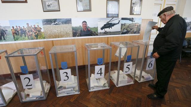Ein älterer Mann legt seinen Stimmzettel in eine gläserne Wahlurne ein.