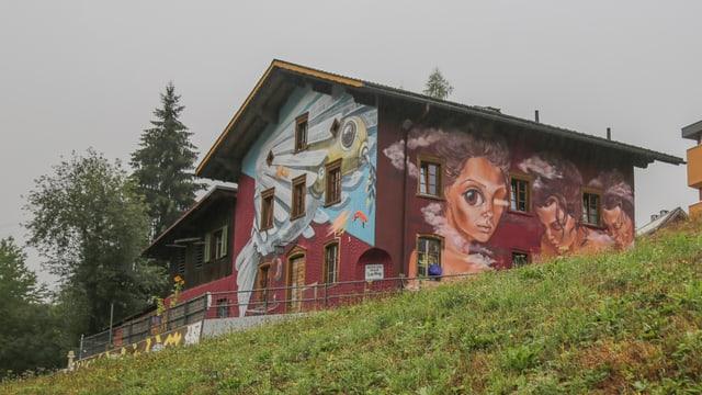 La chasa «Hostel Autra Caussa» cun la fasada da grafittis.