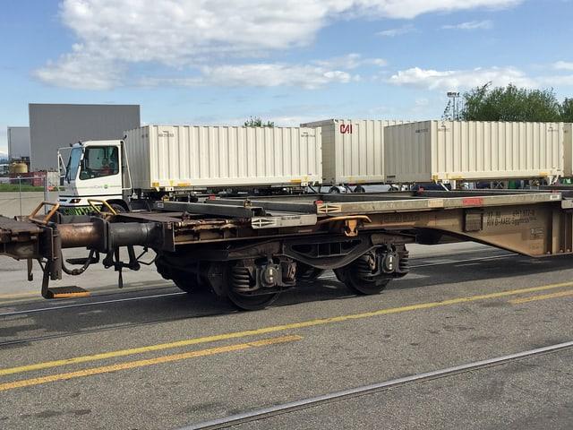Leerer Güterwagen, im Hintergrund Transportlastwagen mit Container