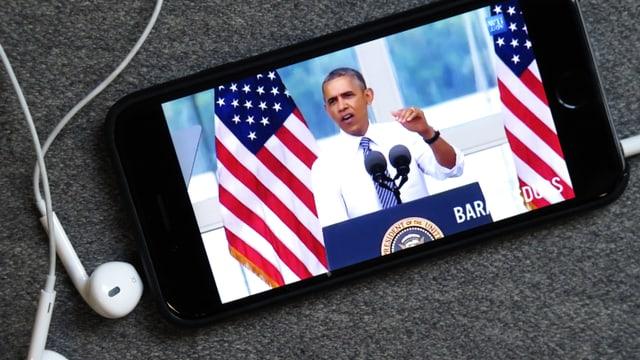 Smartphone mit Kopfhörern und einem Bild von Barack Obama drarauf.