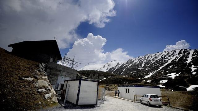 Die Unterkunft, im Vordergrund ein Autot, im Hintergrund Berge.