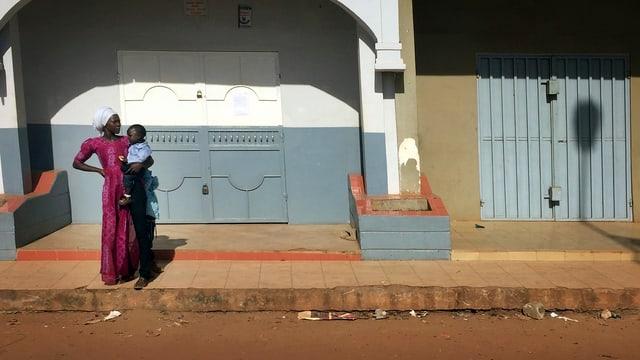 Eine Frau mit einem Kind auf dem Arm steht einsm vor einem verschlossenen Haus.