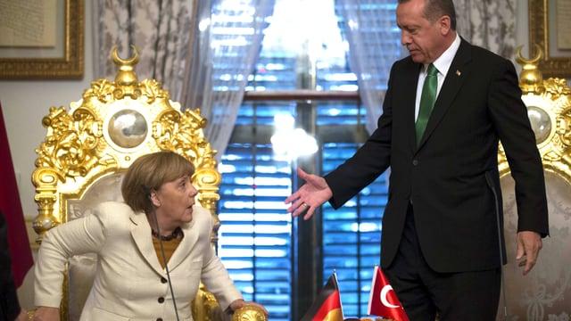 Die deutsche Bundeskanzlerin Angela Merkel wird sitzend überrascht vom Händedruck des türkischen Staatschefs Recep Tayyip Erdogan.