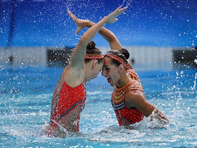Schwimmerinnen drücken die Stirn aneinander.