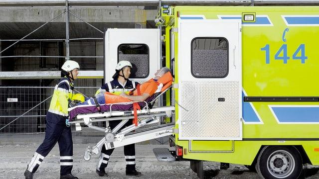 dus sanitaris mettan in pazient en ina ambulanza