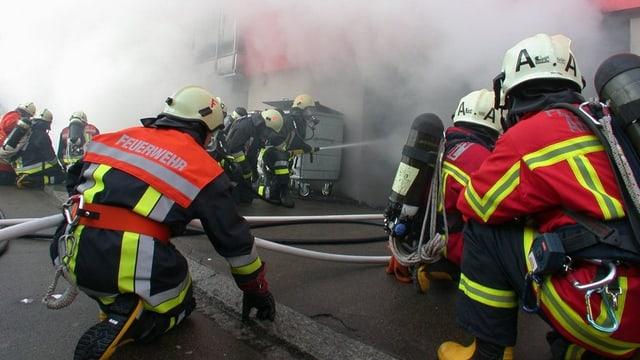 Feuerwehrmänner, Schläuche, Rauch aus einer Tiefgarage