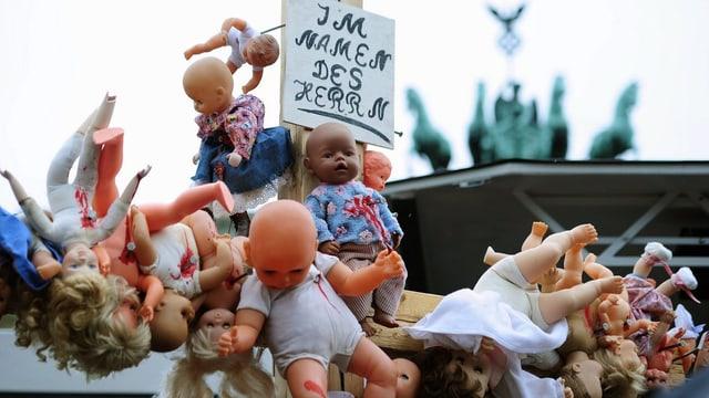 Missbrauchsopfer in Deutschland demonstrieren mit blutigen Puppen an einem Kreuz.