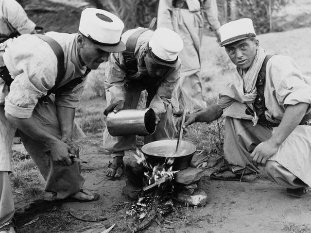 Soldaten kochen auf offenem Feuer.