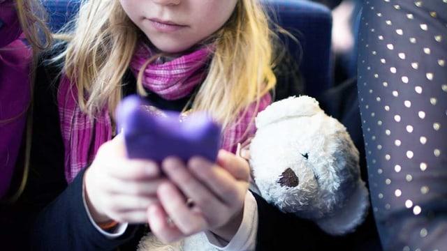 Der Griff zum Smartphone: Ein Mädchen hält Teddybär und Handy in der Hand.