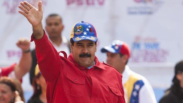 Maduro mit Hut in rotem Hemd winkt der Menge zu.