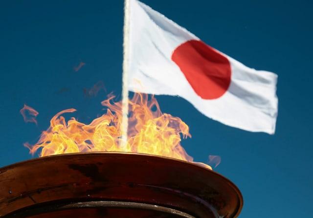 Japanische Fahne und das olympische Feuer im Hintergrund