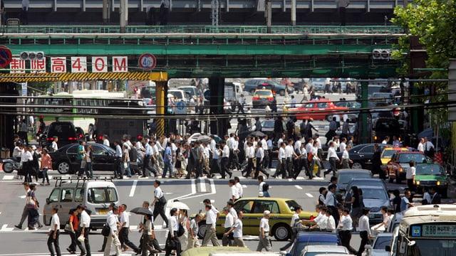 Leute überqueren die Strasse in Japanischer Stadt