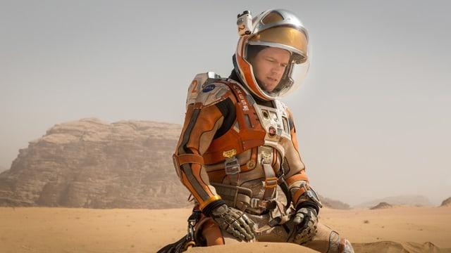 Mann Damon in Weltraumanzug in Wüste kniend