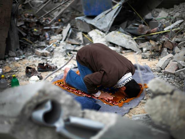 Mann auf Gebetsteppich inmitten von Trümmern.