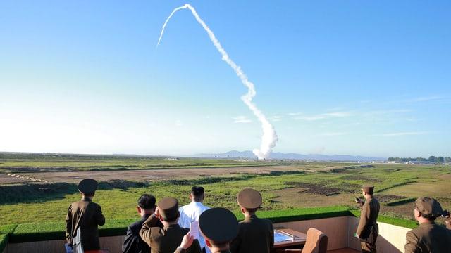 Un sieht von Militärs umringt einem Raketentest zu.