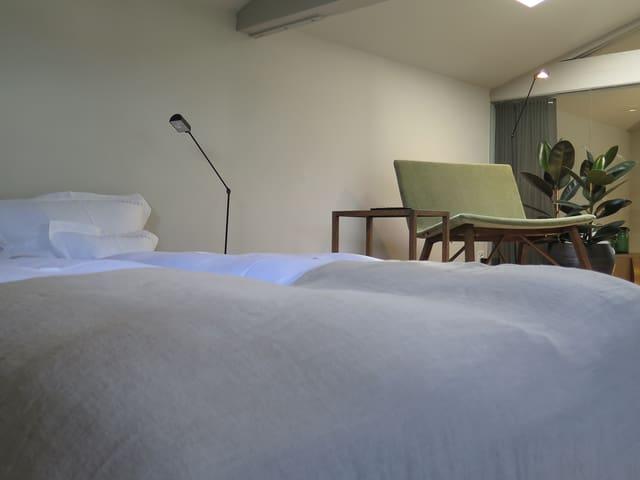 Doppelbett und grüner Sessel