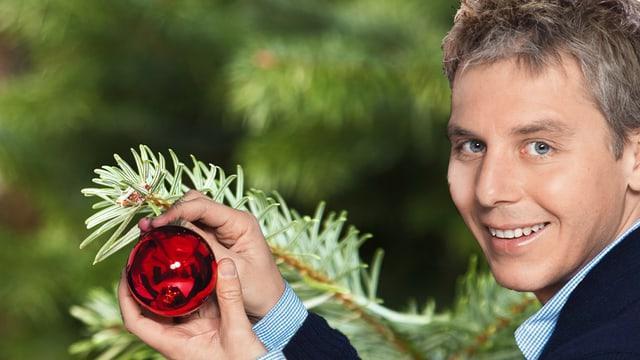 Reto Scherrer vor Tannenbaum mit einer roten Kugel in den Händen.