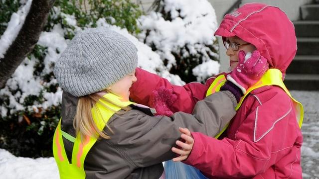 Zwei Kinder seifen sich mit Schnee ein.