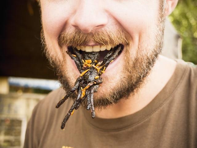 Einem Mann hängt eine gegrillte Tarantel aus dem Mund.