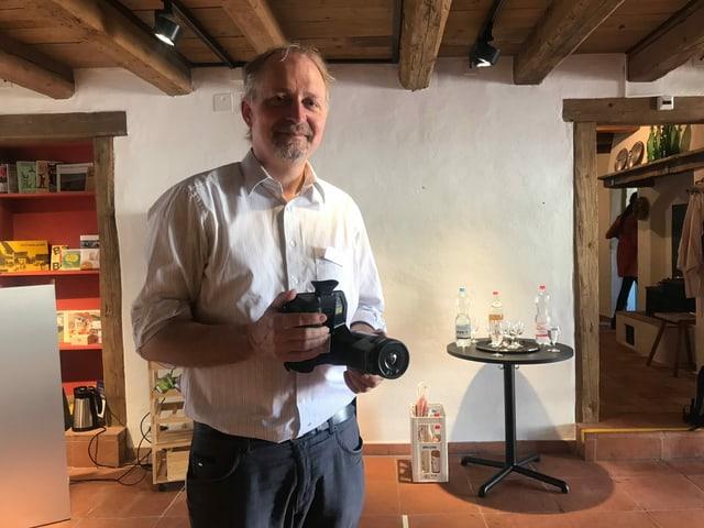 Kantonsarchäologe Reto Marti hält eine Kamera in der Hand.