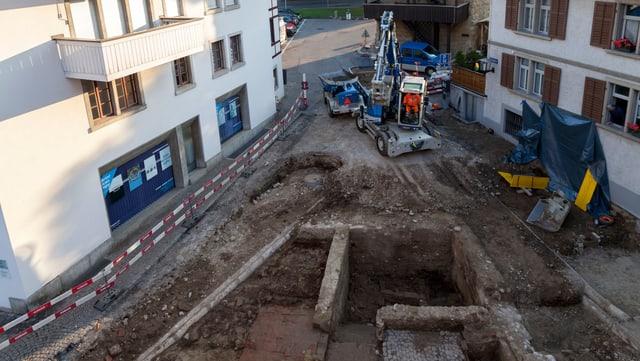 Platz mit historischen Mauern, im Hintergrund Bagger