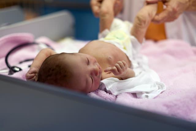 Ein Säugling auf einer Wickelkomode.