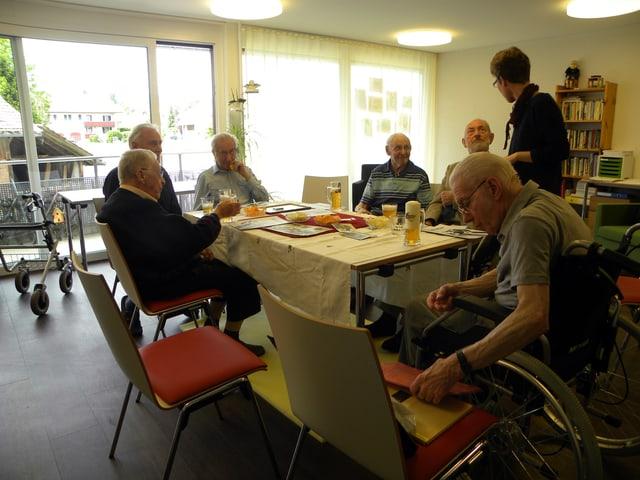 Sechs Männer sitzen in einem grossen Zimmer an einem Tisch.