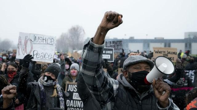 Viele Menschen mit Maske halten Schilder oder ihre Fäuste in die Höhe. Ein Mann spricht in ein Megafon.