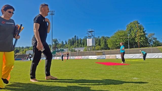 Remo Murer läuft über Rasen, im Hintergrund Damen auf Turnmatten