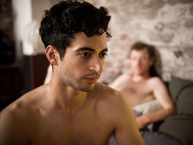 Filmszene ein junger Mann mit nacktem Oberkörper. Im Hintergrund liegt auf einem Bett ein nackter Mann.