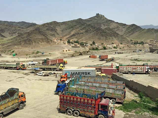 Viele Lastwagen stehen auf Wüstensand, hinten sind trockene Hügel zu sehen. Die Grenze ist fast nicht erkennbar, neu eine kleine Mauer ist zu sehen.