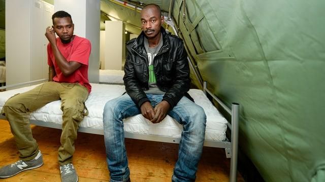 Zwei Männer sitzen auf einem Bett in einem Zelt.