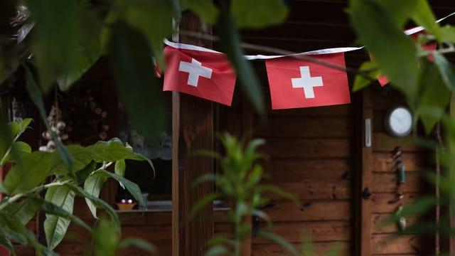 Schweizer Fähnchen hängen vor einer Holzfassade.