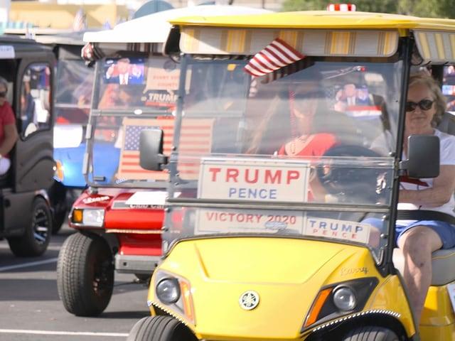 Menschen in Golfwagen mit Wahlplakaten